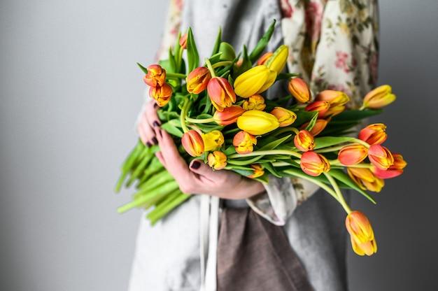Femme tient un bouquet de tulipes jaunes, orange et rouges
