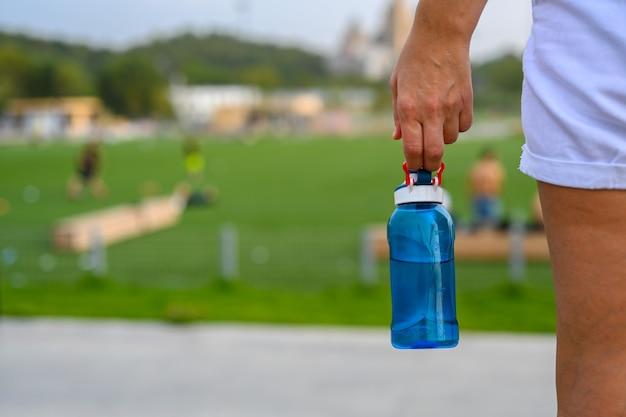 Une femme tient une bouteille d'eau sur le fond d'un terrain de sport pour le football, le rugby et l'entraînement. fermer.