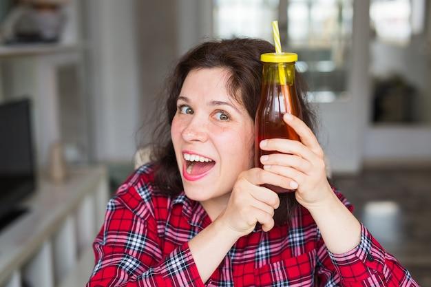Femme tient une bouteille de jus de fruits frais