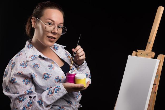 La femme tient la brosse et les peintures sur le noir