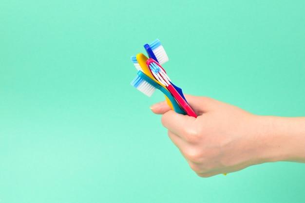 La femme tient des brosses à dents dans sa main sur green