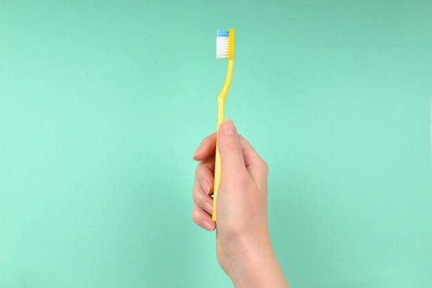 La femme tient des brosses à dents à la main sur un fond vert.