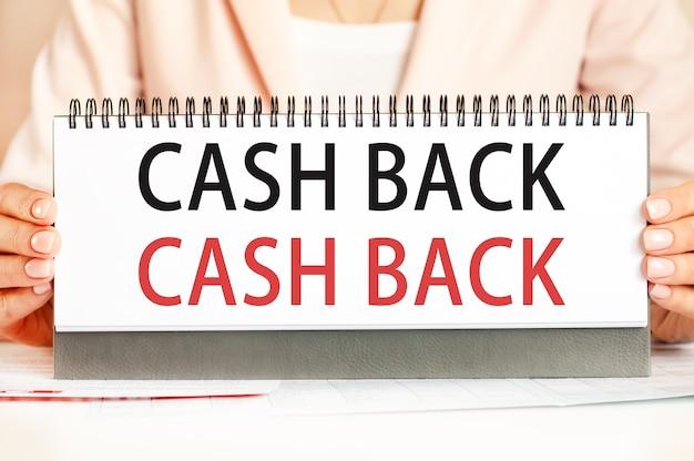 La femme tient un carton avec les mains avec le texte cash back