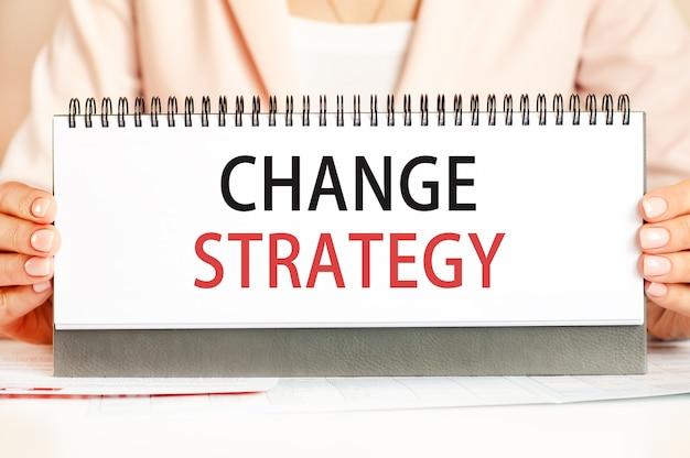 La femme tient un carton avec les mains avec le texte stratégie de changement