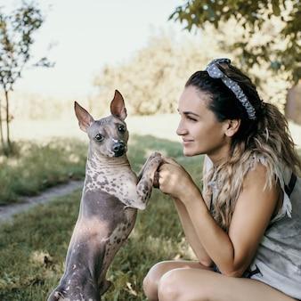 La femme tient le chien par les pattes sur un fond de parc