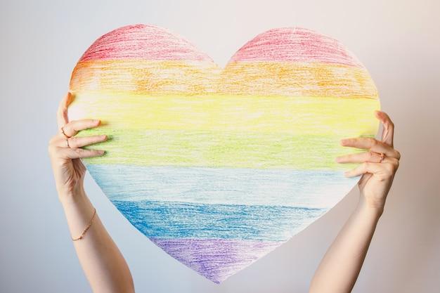 Une femme tient un coeur arc-en-ciel sur un mur blanc symbole de la communauté lgbt