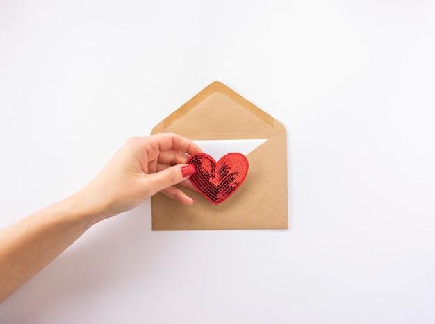 Une femme tient un cœur rouge dans sa main prêt à l'envoyer comme carte postale