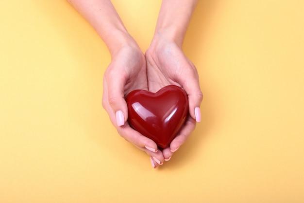 Une femme tient un coeur rouge dans ses mains