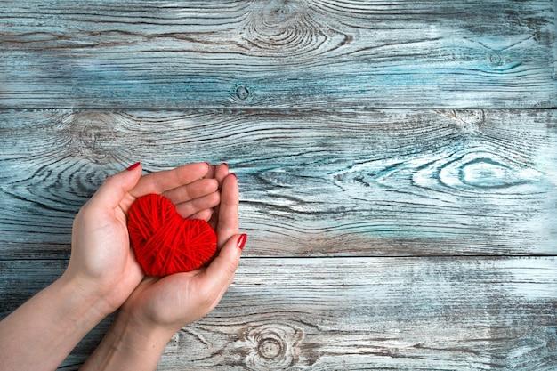 Une femme tient un coeur rouge sur un fond en bois bleu-gris.