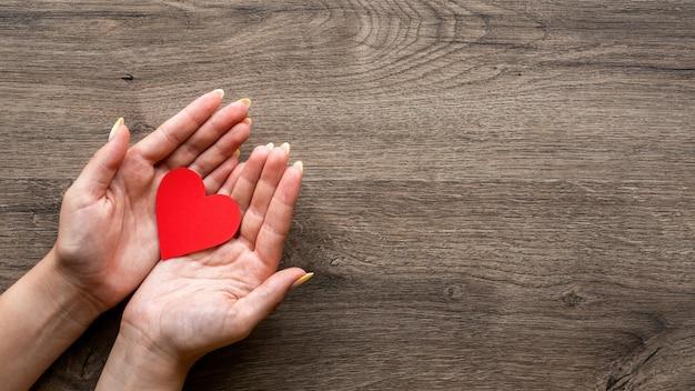 Femme tient un coeur rouge