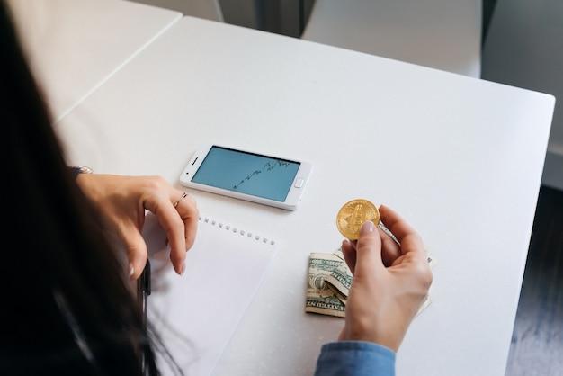 La femme tient une crypto-monnaie sur le fond du programme