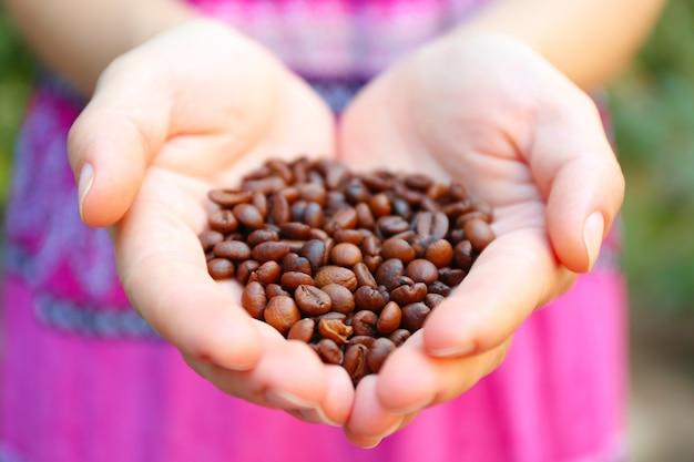 La femme tient dans les mains des grains de café torréfiés, en forme de coeur