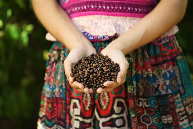 Femme tient dans les mains des grains de café torréfiés