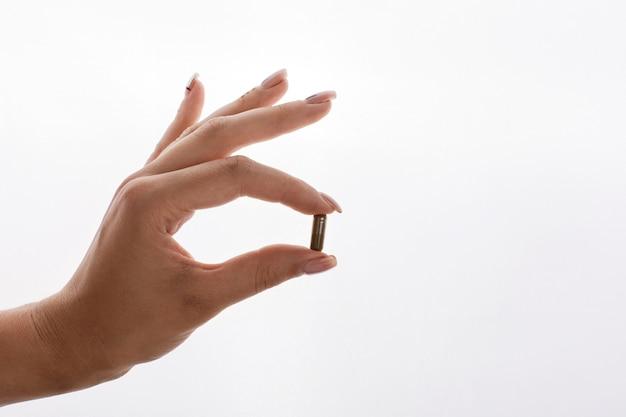 Femme tient dans sa main une capsule avec des vitamines ou de l'huile