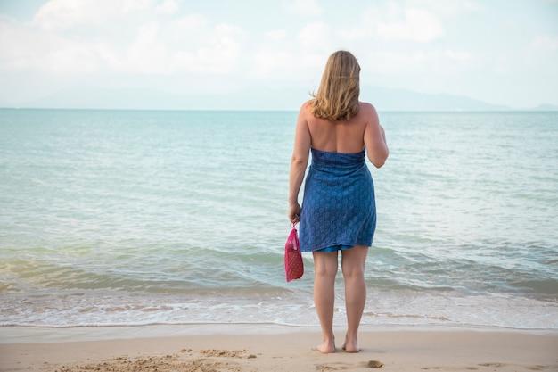 Une femme tient dans sa main un sac en filet et se tient au bord de la mer sur une plage de sable. notion d'écologie. consommation consciente