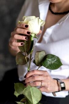 Femme tient dans sa rose blanche avec une longue tige gros plan