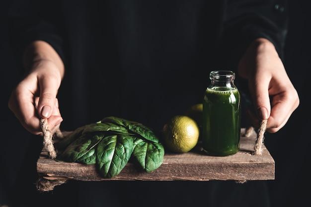 Femme tient dans ses mains un plateau vintage avec smoothie aux épinards, citron vert et épinards.