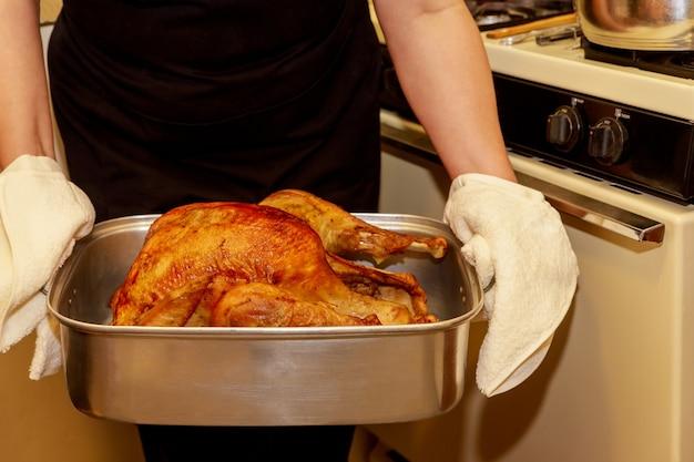 Une femme tient une dinde croustillante au four pour le jour de thanksgiving ou noël.