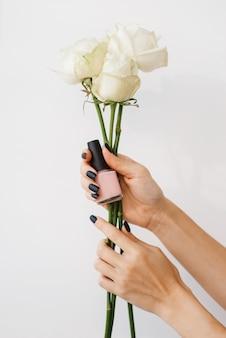 Femme tient du vernis à ongles et des fleurs, salon de beauté