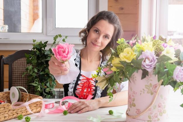 Une femme tient une fleur dans ses mains. plantes en matériaux artificiels fabriquées par un fleuriste pour le design.