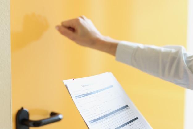 Une femme tient un formulaire de demande dans sa main et frappe à la porte
