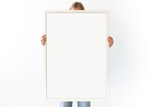 Femme tient un grand cadre photo blanc