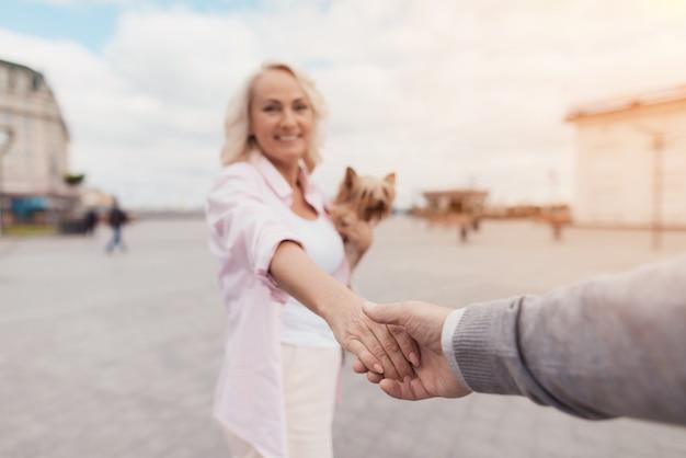 Une femme tient un homme par la main et mène