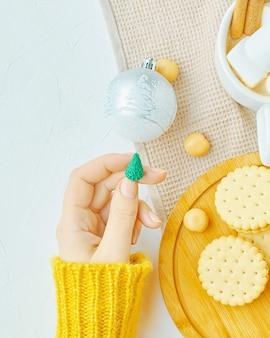 Une femme tient un jouet de noël dans sa main une tasse de café avec des guimauves et des biscuits à la cannelle sur un plateau...