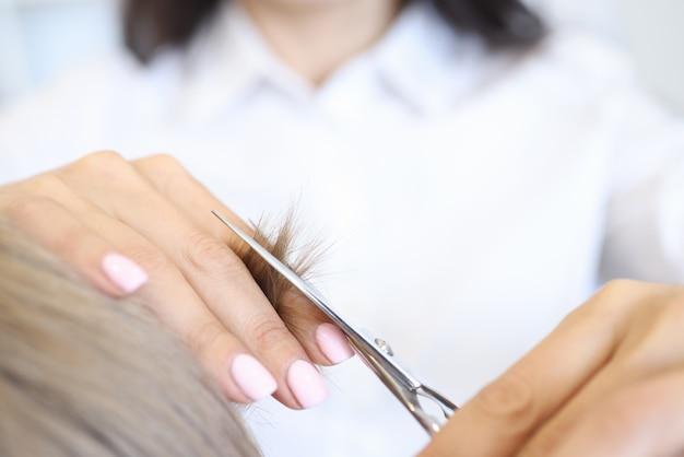Femme tient une mèche de cheveux avec sa main et coupe avec des ciseaux avec l'autre main