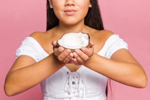 Une femme tient la moitié de la noix de coco