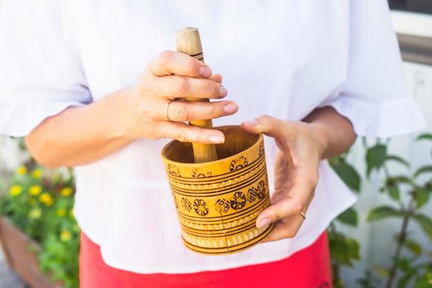 Une femme tient un mortier en bois rustique dans ses mains et malaxe la menthe poivrée