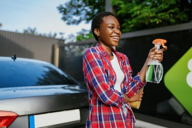 Une femme tient un nettoyant pour vitres, une station de lavage de voiture à la main
