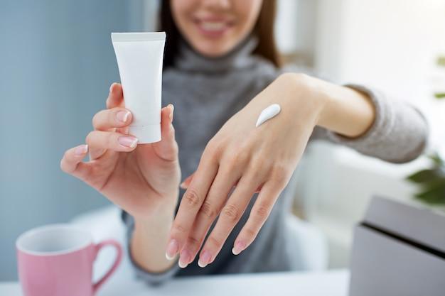 Femme tient un petit tube de crème pour les mains dans une main et montre son autre main avec de la crème dessus