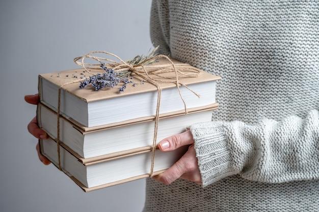 Femme tient une pile de livres de poche enveloppés de ficelle et décorés de lavande
