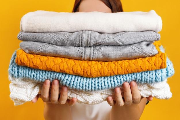 Une femme tient une pile de vêtements chauds en tricot