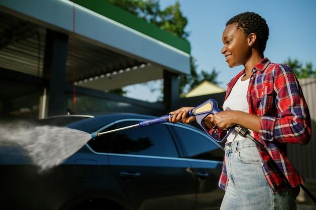 La femme tient le pistolet à eau à haute pression, lavage de voiture