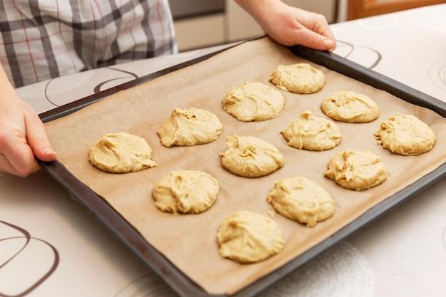 Une femme tient une plaque à pâtisserie avec des biscuits crus. cuisine à la maison.
