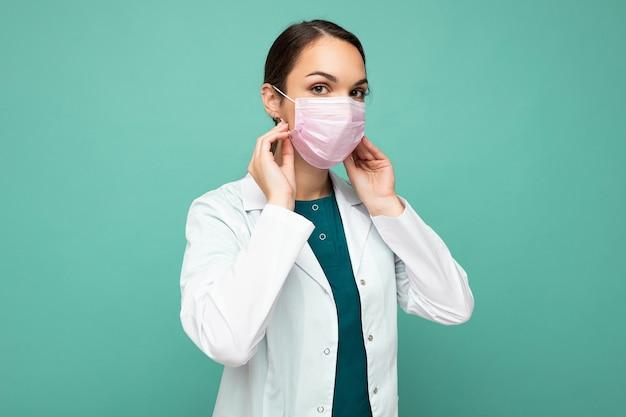 Femme tient et porte un masque médical blanc