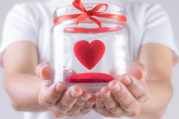 La femme tient un pot avec un cœur rouge à l'intérieur