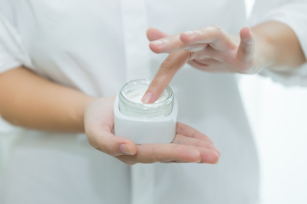 Femme tient un pot avec une crème cosmétique dans ses mains