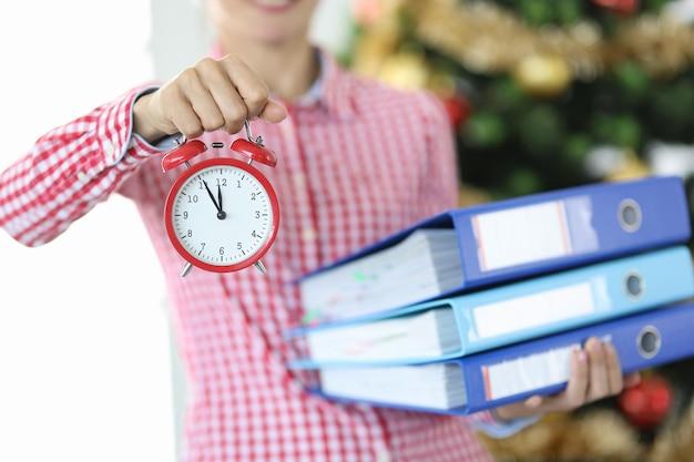 Une femme tient un réveil pour midi et une pile de documents sur fond de