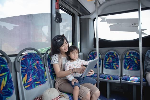 Femme tient sa fille sur ses genoux et montre une tablette