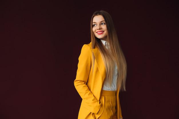 La femme tient sa main dans la poche du costume jaune et sourit sur l'espace du mur.