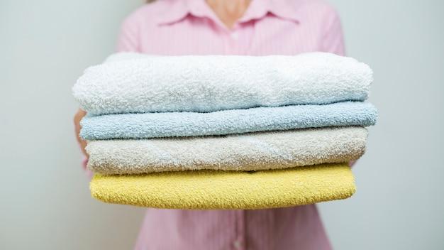 Une femme tient des serviettes propres pliées.