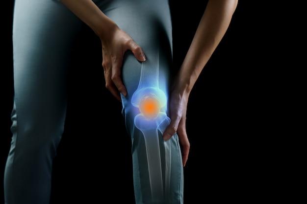 Femme tient ses mains au genou, douleur au genou surlignée en bleu, médecine, concept de massage.