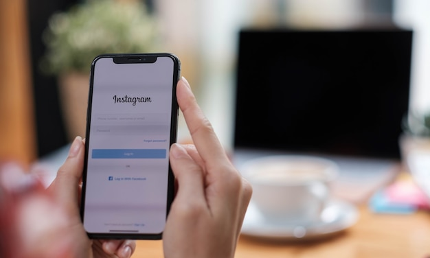 Une femme tient un smartphone avec une application instagram sur l'écran du café. instagram est une application de partage de photos pour smartphones.