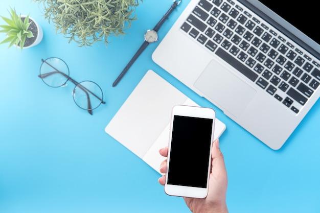 Une femme tient un smartphone isolé avec un espace de bureau bleu minimal, plat, vue de dessus, maquette