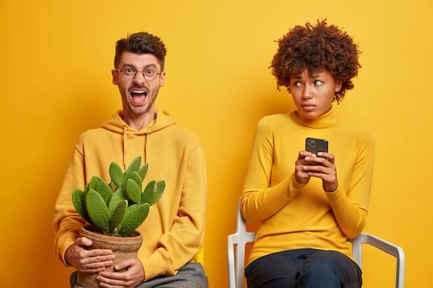 Une femme tient un smartphone moderne et un homme crie en tenant une plante
