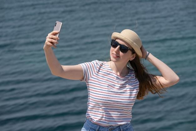 Une femme tient son chapeau avec sa main et se filme en utilisant son téléphone au bord du lac. temps venteux. loisirs de plein air, loin de la grande ville. fermer.