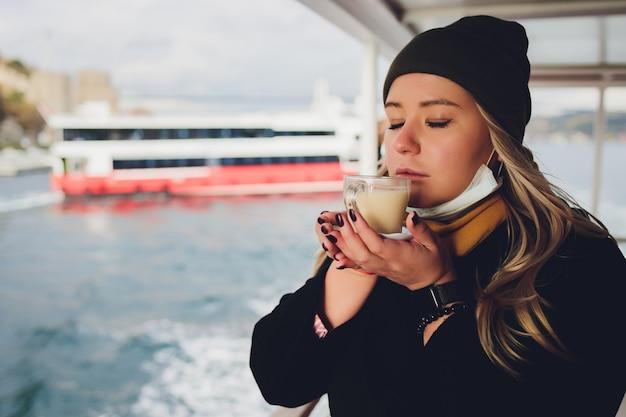 Femme tient une tasse blanche de boisson lactée chaude avec de la cannelle dans le paysage marin.